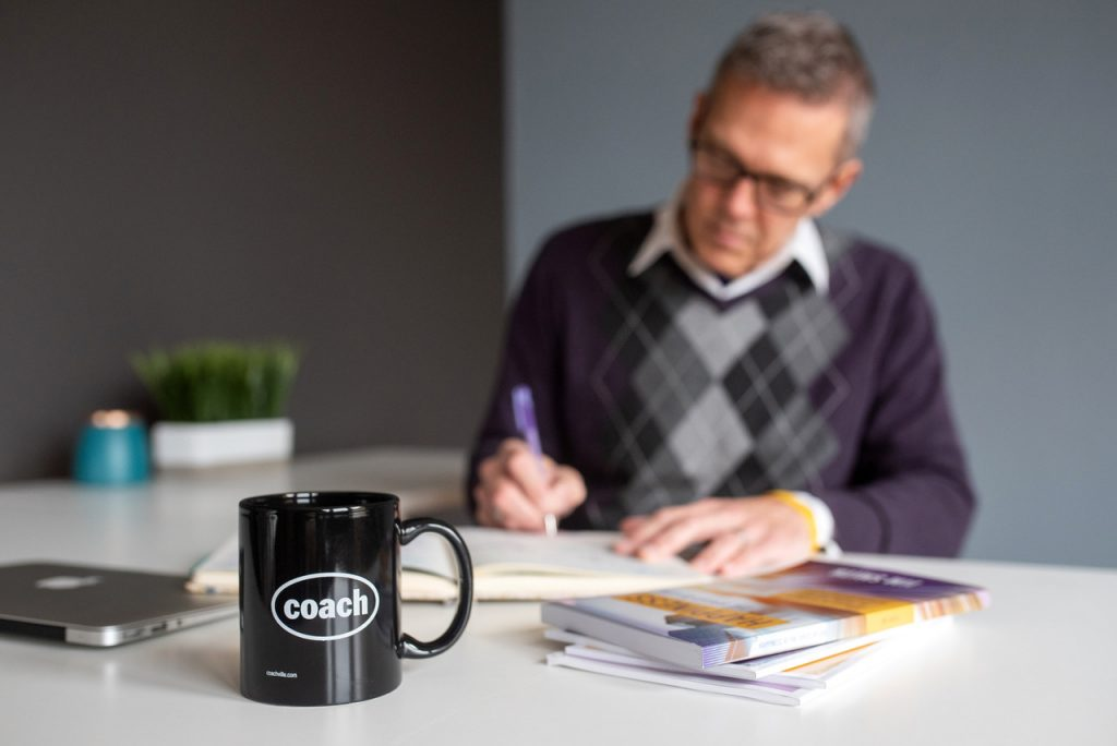 "Act Happy Week, Day 4 - Jim sitting at a desk writing happiness exercises with a coffee cup that reads ""Coach"" in the forefront."
