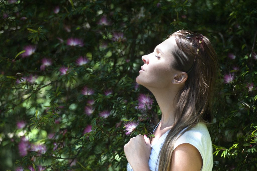 Act Happy Week, day 5: woman breathing in fresh air by a beautiful flowering tree.